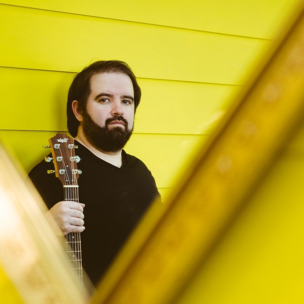 Brian Wolff with acoustic guitar on yellow backdrop