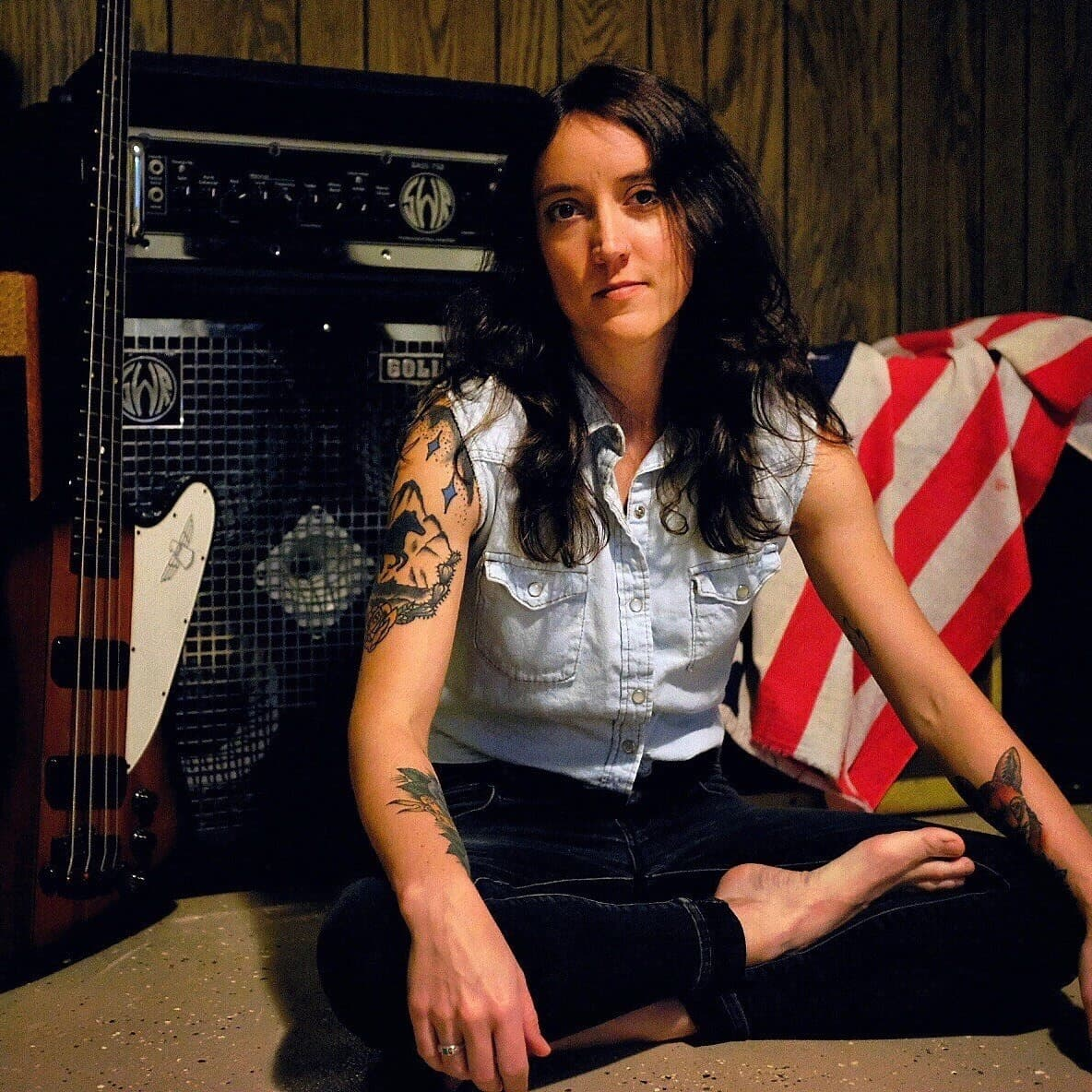 Sylvia Rose Novak sitting in front of her amp, a bass guitar and American flag
