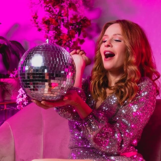 Hiedi Webster looking at a mirror ball, in glamorous attire on pink background