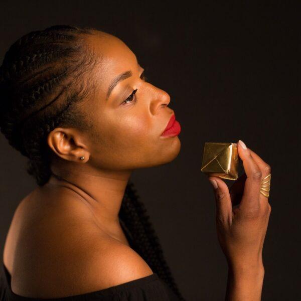 Joy Ike holding tiny gift box on black background