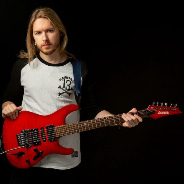 British guitarist composer Timothy Reid holding red electric guitar