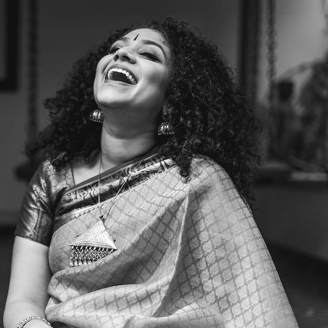 Carnatic singer Roopa Mahadevan smiling and laughing with head tilted back