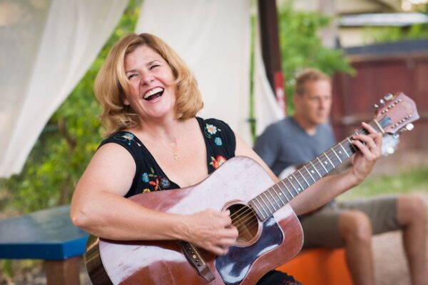 Tanya Winch playing acoustic guitar smiling