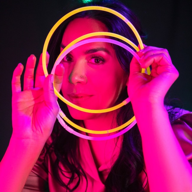 Recording artist Amiena lit in pink holding neon glow circles in front of face, representing halos