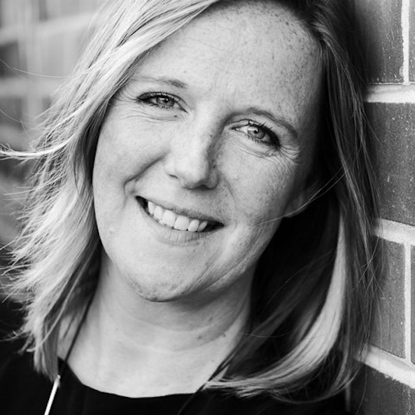 Lynz Crichton, musician and creator of Music Marketing Method, black & white headshot leaning against brick wall, smiling