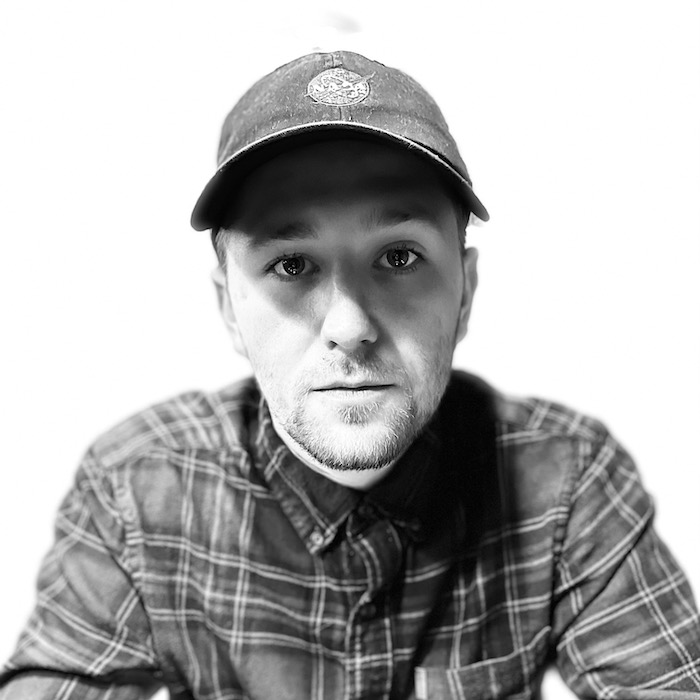 Andrew Chris, black & white photo, wearing ball cap and a flannel shirt on a white background