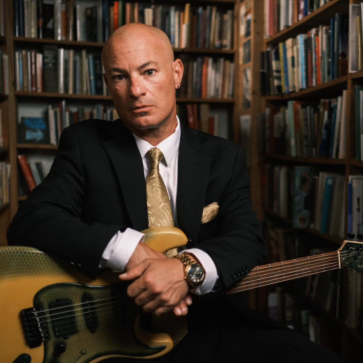 Ryan Rosoff of Little King sitting in library with guitar in suit and tie